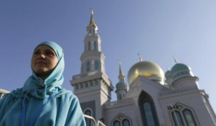 A volunteer and participant of Moscow Grand Mosque's opening ceremony stands outside the mosque in Moscow, Russia, September 23, 2015. The new mosque, which was erected on the site of the city's original mosque built in 1904 and which has been under reconstruction since 2005, will be able to accommodate up to 10,000 people simultaneously, according to local media. REUTERS/Maxim Shemetov  - RTX1RZCI
